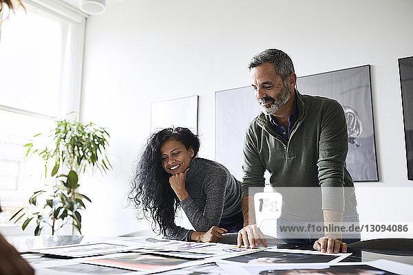 Niedrigwinkelansicht von Geschäftsleuten  die Fotoausdrucke im Konferenzraum untersuchen