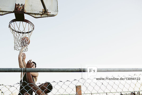 Low angle view of friends playing basketball against clear sky