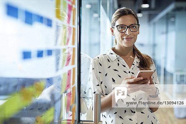 Portrait of smiling businesswoman holding smart phone while standing by glass door in office