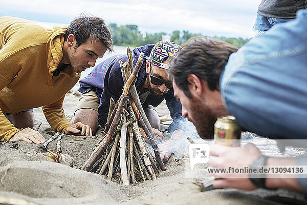Male friends preparing campfire on sand at riverbank