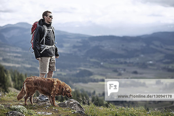 Hiker with dog standing on mountain against sky