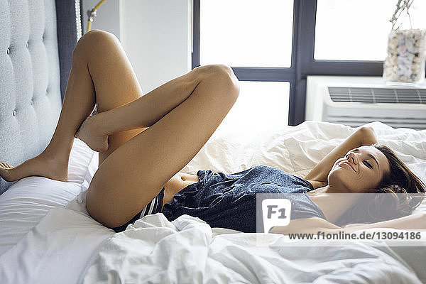 Smiling sensuous woman relaxing on bed