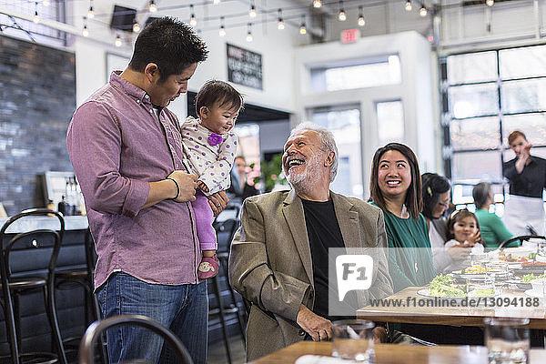 Glücklicher Mann schaut sich an  wie ein kleines Mädchen im Restaurant vom Vater getragen wird