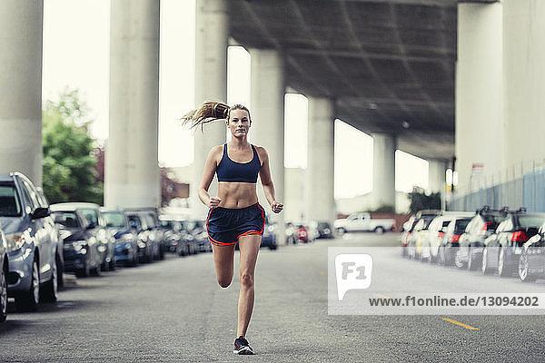 Full length of determined female athlete running on street under bridge