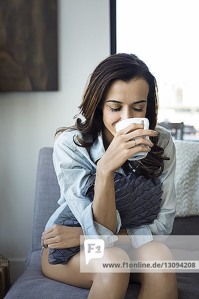 Woman holding cushion drinking while sitting on sofa