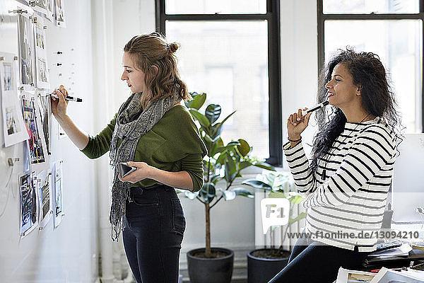 Geschäftsfrau betrachtet weibliche Kollegin  die am schwarzen Brett im Büro schreibt