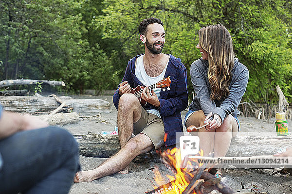 Man playing ukulele while sitting with friends by campfire at riverbank