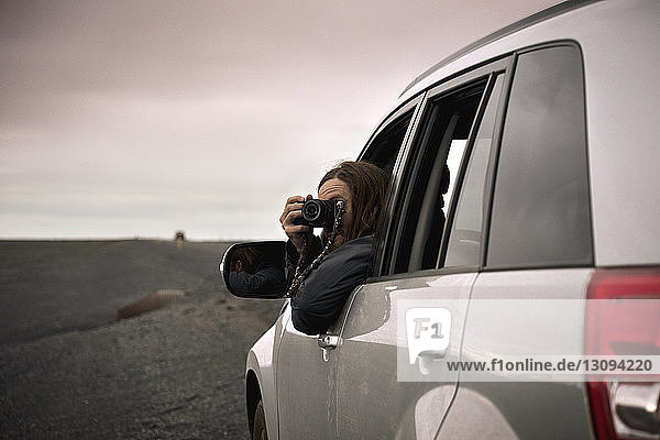 Man photographing through camera while sitting in off-road vehicle