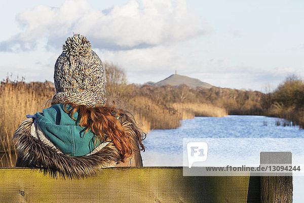 Rückansicht einer Frau,  die im Winter auf einer Bank am Flussufer sitzt