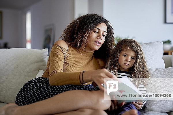Niedriger Blickwinkel auf Mutter liest Bilderbuch für niedliche Tochter  während sie zu Hause auf dem Sofa sitzt