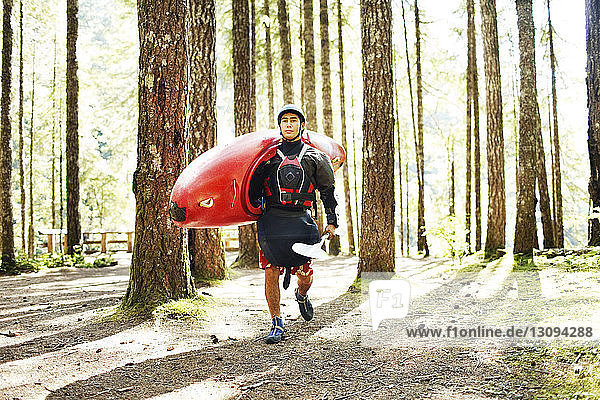 Man carrying kayak while walking in forest