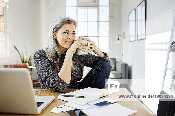 Portrait of woman holding coffee mug while working at table in living room