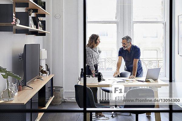 Geschäftsmann diskutiert mit Kollege im Kreativbüro durch Fenster gesehen