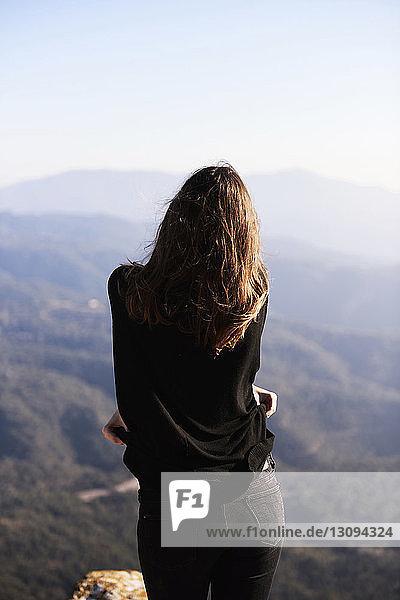 Rückansicht einer Frau  die einen Pullover hält  während sie gegen den Himmel steht