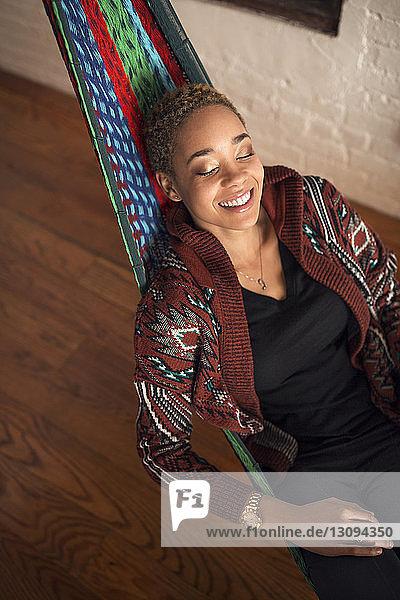 Draufsicht einer glücklichen Frau  die zu Hause auf einer Hängematte schläft