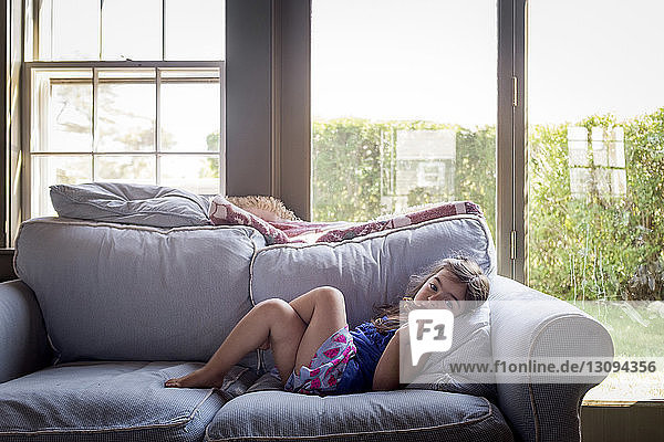 Portrait of girl lying on sofa by window at home