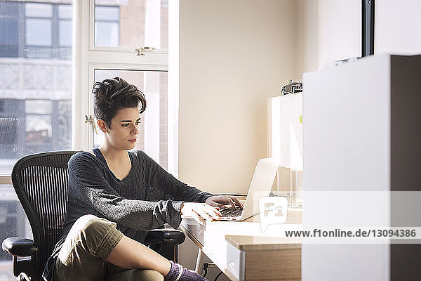 Confident woman using laptop computer at home