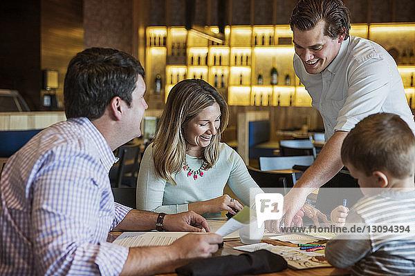 Fröhlicher Kellner hilft der Familie beim Lesen der Speisekarte am Restauranttisch