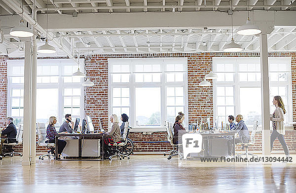 Business people working at desks by window in office