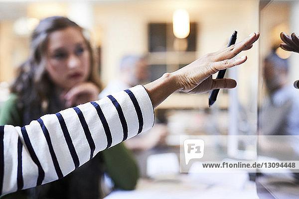Abgehackte Hand einer Geschäftsfrau  die am Desktop-Computer gestikuliert  während sie mit einer Kollegin im Büro zusammenarbeitet