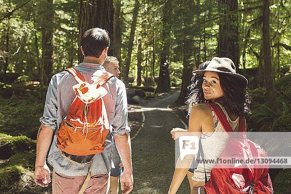 Porträt einer Frau  die mit Freunden auf einer Straße im Wald wandert