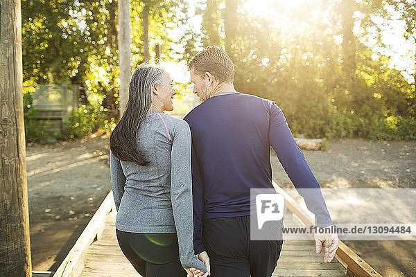Rear view of couple holding hands and walking on boardwalk