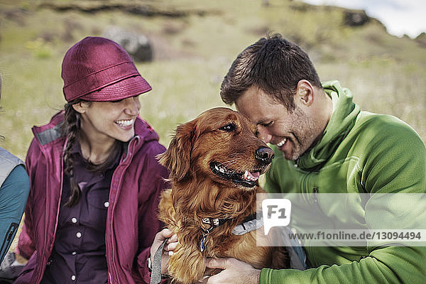 Happy hikers with dog sitting on hill