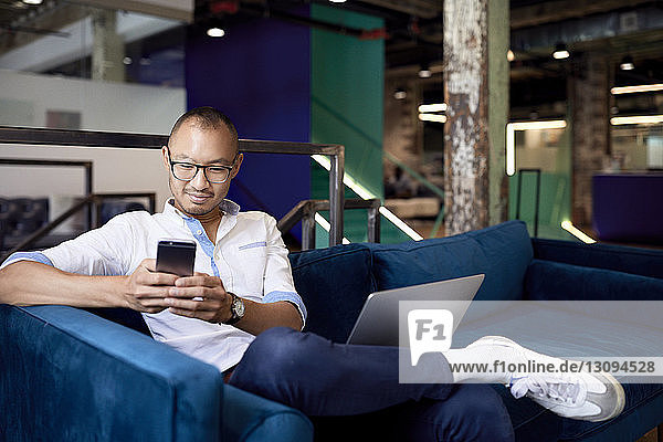 Smiling businessman using mobile phone while sitting on sofa at office