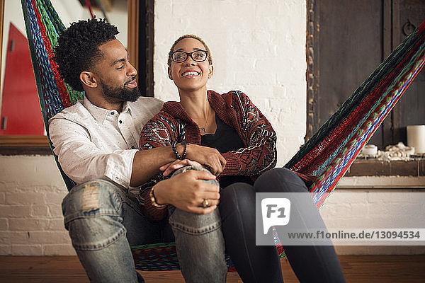 Glückliches junges Paar sitzt zu Hause auf der Hängematte