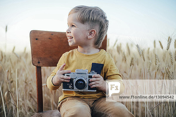 Cheerful boy with camera looking away while sitting on chair amidst wheat field