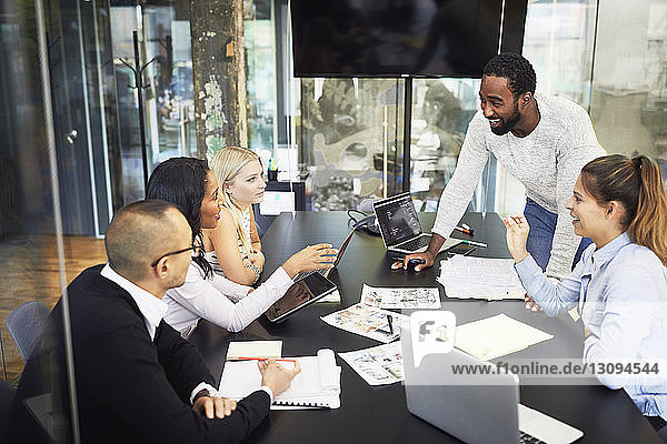 High angle view of smiling multi-ethnic business people discussing in meeting at board room