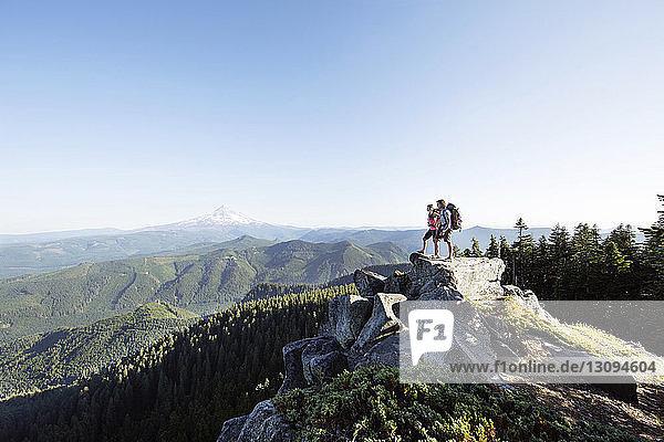 Paar steht auf Berg gegen klaren Himmel