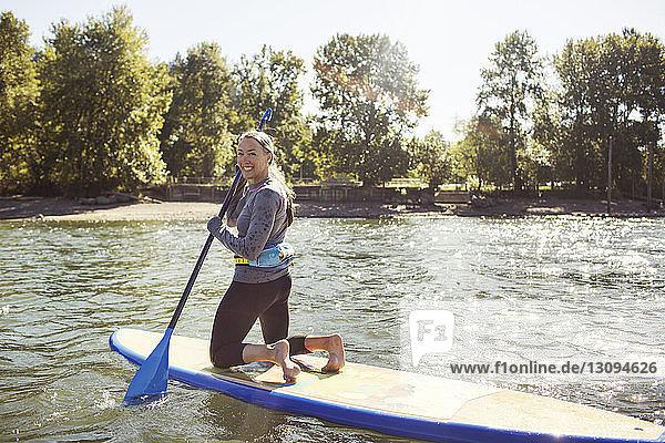 Porträt einer lächelnden Frau beim Paddelbootfahren auf einem Fluss