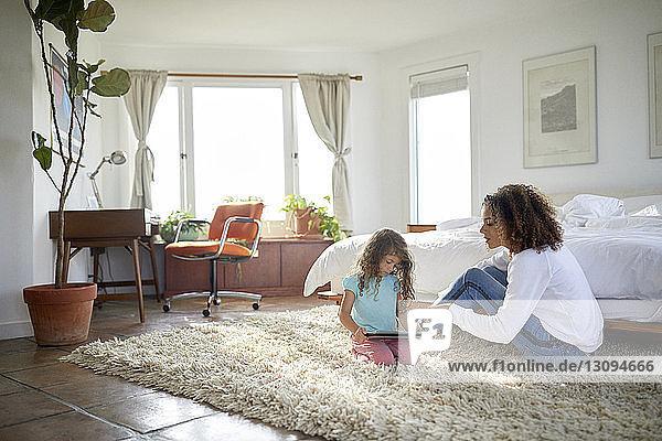 Mutter sieht Tochter am Tablet-Computer an  während sie auf dem Teppich im Schlafzimmer sitzt