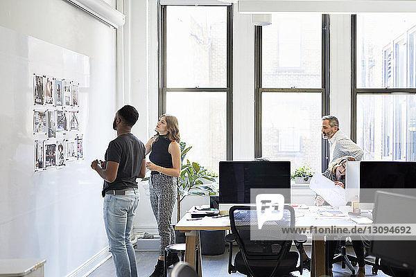 Geschäftsleute betrachten Fotoausdrucke am Schwarzen Brett,  während Kollegen im Büro arbeiten