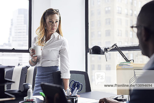 Businesswoman looking at male colleague while holding coffee cup against window in office