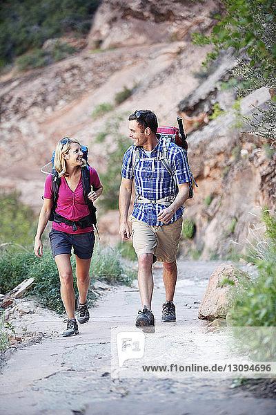 Glückliches Paar geht auf Straße gegen Berg