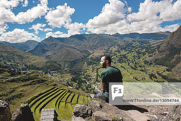 Rear view of hiker looking at view while sitting on mountain against sky at Pisac
