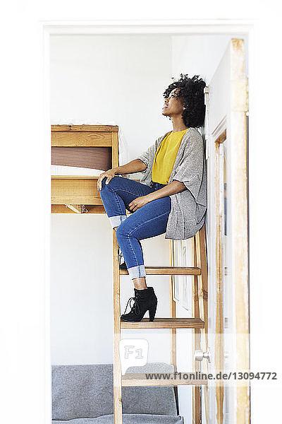 Frau schaut auf  während sie auf einer Etagenbettleiter sitzt und durch die Tür gesehen wird