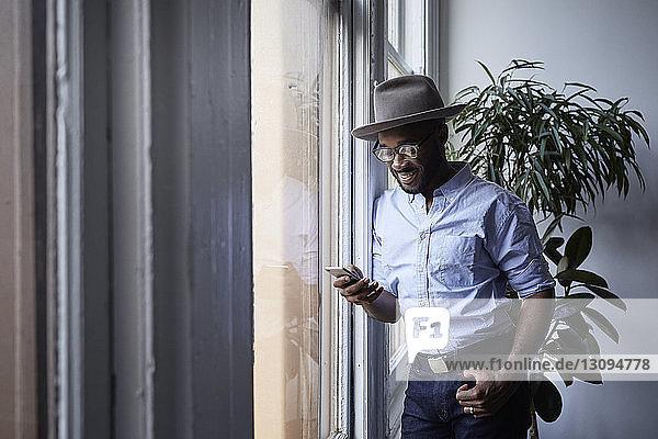Lächelnder Geschäftsmann,  der ein Mobiltelefon benutzt,  während er im Kreativbüro am Fenster steht