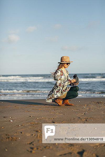 Frau hält Kamera und hockt am Strand gegen den Himmel am sonnigen Tag