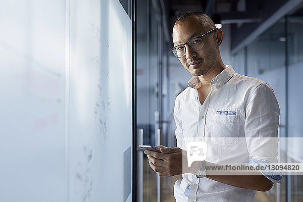 Portrait of businessman holding smart phone while standing at office