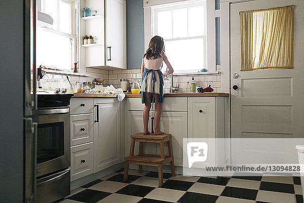 Rear view of girl washing dish in kitchen at home