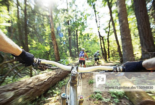 Ausgeschnittenes Bild einer Person  die mit Freunden im Wald Fahrrad fährt