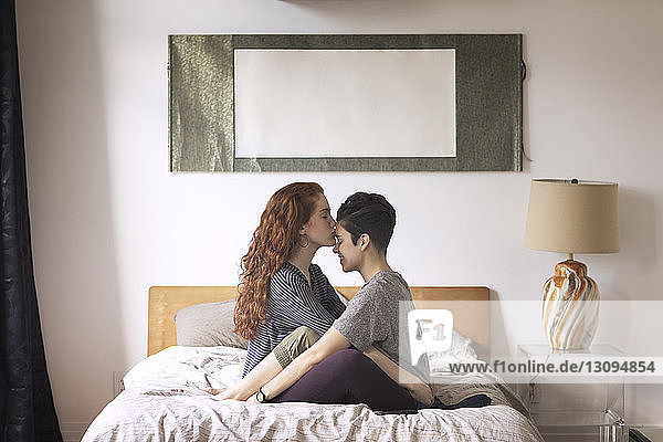Romantic lesbian kissing on girlfriend's forehead while sitting on bed at home