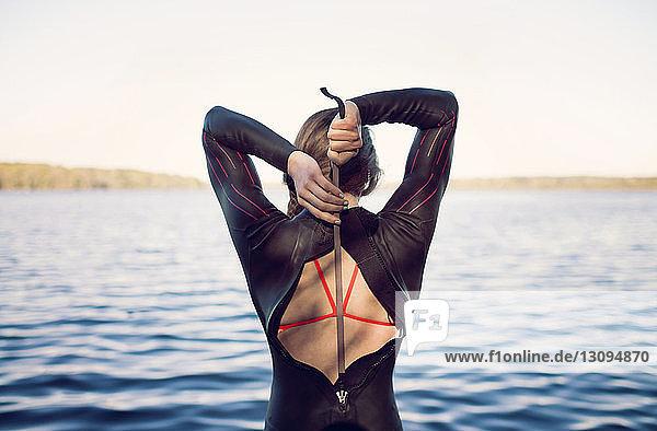Rückansicht eines Schwimmers im Neoprenanzug am Seeufer