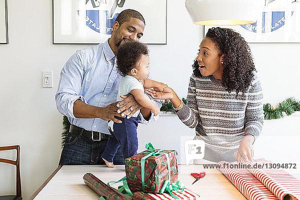 Glückliche Eltern spielen mit ihrem Sohn am Tisch