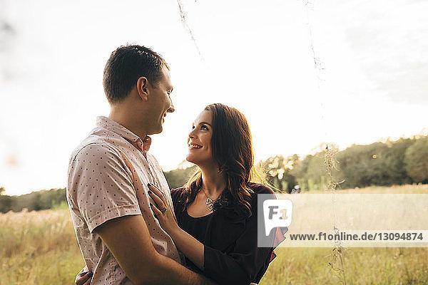 Ein Paar sieht sich an  während es auf einem Grasfeld vor klarem Himmel steht