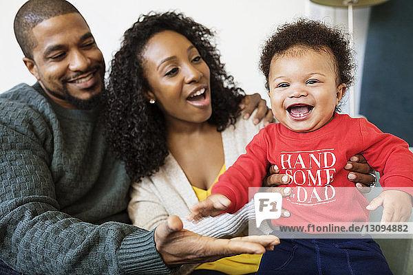 Fröhlicher kleiner Junge spielt mit den Eltern zu Hause