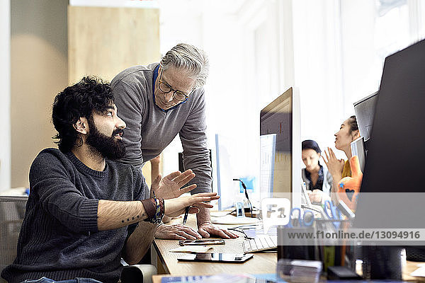 Businessmen discussing over desktop computer with female colleagues sitting in background